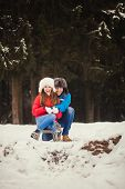 picture of sled  - funny couple sitting in a sled and smiling - JPG