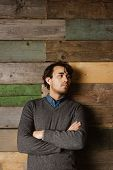 pic of arms race  - Handsome young business man leaning against a wooden wall with his arms crossed looking away - JPG