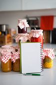 foto of pickled vegetables  - Closeup on notepad among jars with homemade fruits jam and pickled vegetables - JPG