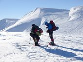 image of north-pole  - Men in snowshoes and with trekking poles go in the mountains - JPG