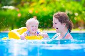 image of swimming pool family  - Happy family young active mother and adorable curly little baby having fun in a swimming pool child learning to swim in an inflatable toy ring enjoying summer vacation at a tropical resort - JPG