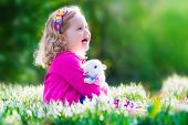 image of petting  - Adorable little girl cute curly toddler in a colorful summer dress playing with a real rabbit having fun with her pet bunny in a beautiful garden with first spring snowdrop flowers - JPG