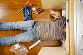 foto of sink  - A man on the kitchen floor is fixing the sink - JPG