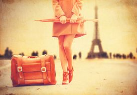 pic of grils  - Gril in coat with umbrella and suitcase in Paris on Eiffel tower background - JPG