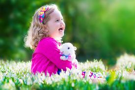 picture of bunny rabbit  - Adorable little girl cute curly toddler in a colorful summer dress playing with a real rabbit having fun with her pet bunny in a beautiful garden with first spring snowdrop flowers - JPG