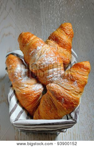 fresh croissants in basket on wooden table