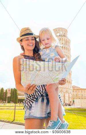 Mother Holding Daughter Looking At Map In Pisa In Summer