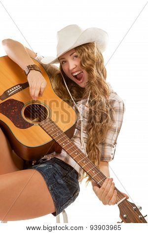 Sesy cowgirl in cowboy hat with acoustic guitar