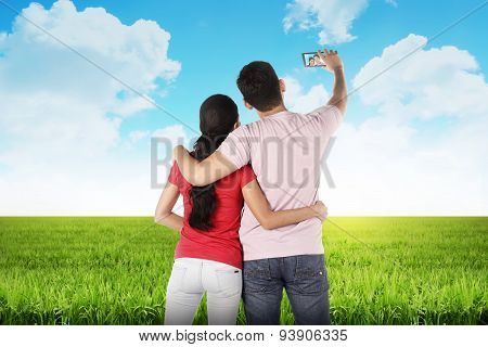 Couple Doing Selfie In The Middle Of The Meadow