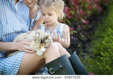 Happy Mother With Her Daughters Holding Cat Against Nature