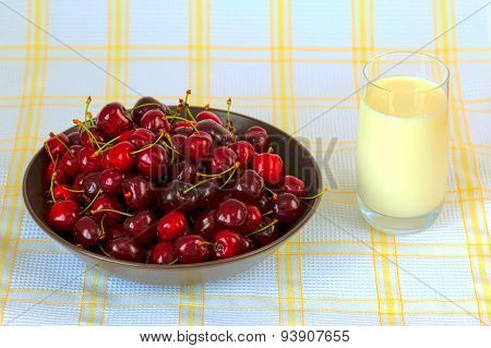Red sweet cherries with water drops and glass of milk