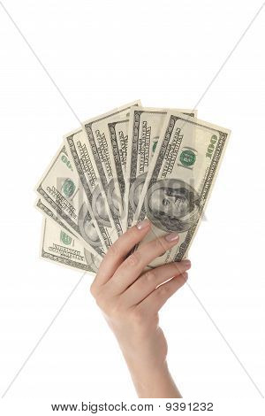 Pile of dollar's banknotes in female hand on white background