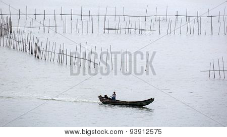XIAPU, CHINA - JUNE 4, 2015: A farm worker returns after inspection of the nets of a large crab farm in the sea in Xiapu, China. Aquaculture is an important driving economic force here.