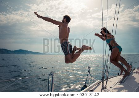 Friends Jumping Into Water From A Sailing Boat