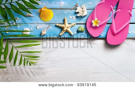 Flip flops and blue wooden on beach with seashells