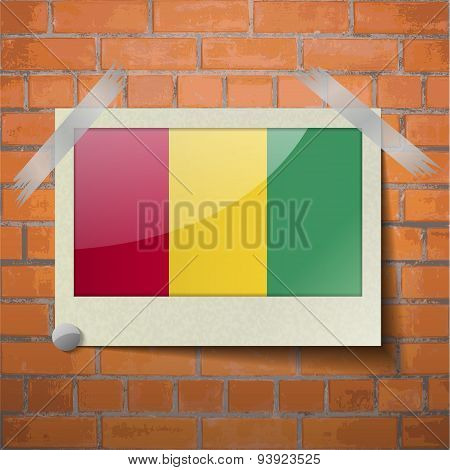 Flags Guinea Scotch Taped To A Red Brick Wall