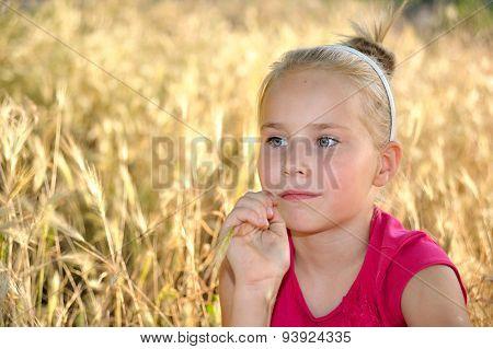 Thoughtful little girl dreaming in wheat field