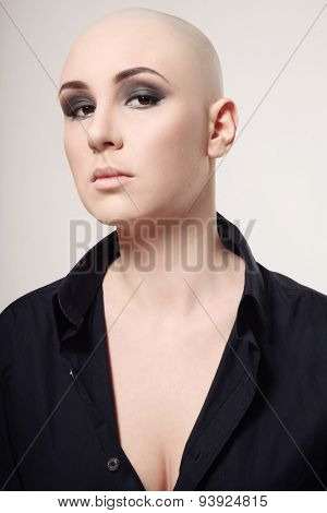 Portrait of young skinhead woman with smoky eyes make-up