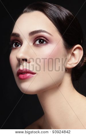 Portrait of young beautiful woman with stylish make-up looking upwards