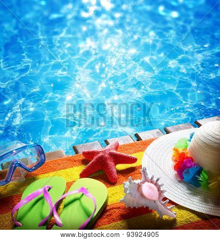 summer holidays in pool - with towel, sandals, hat and shell