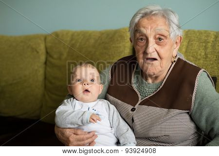 Baby And Elderly Woman Looking At Camera