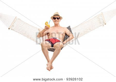 Carefree senior in red swim trunks lying in a hammock and drinking a delicious orange cocktail isolated on white background