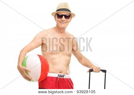 Senior in swim shorts holding a beach ball and a bag isolated on white background