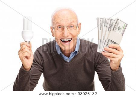Delighted senior gentleman holding an energy saving light bulb and four stacks of money isolated on white background