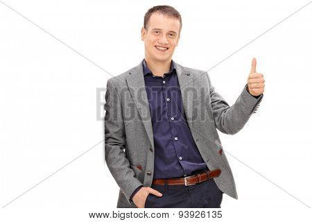 Handsome young man leaning against a wall and giving a thumb up isolated on white background