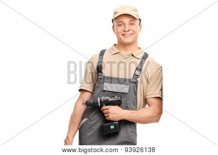 Young worker in gray uniform holding a hand drill and leaning against a wall isolated on white background