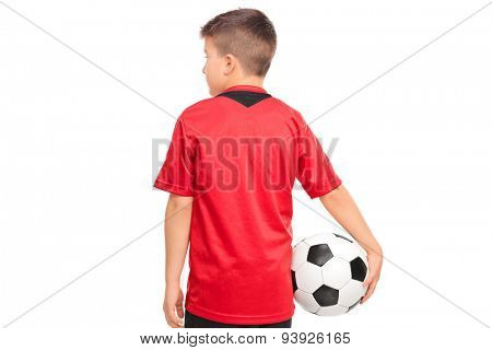 Junior soccer player holding a ball isolated on white background, rear view