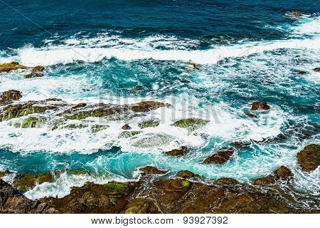 Stones In Waves With Foam On Coast