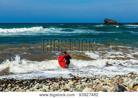 Surfer With A Surfboard In Atlantic Ocean Coast