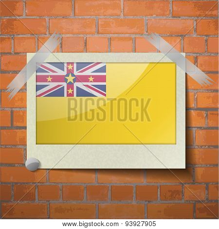 Flags Niue Scotch Taped To A Red Brick Wall