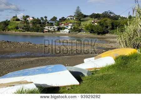Upturned old classic colorful dinghy boats on the ground during low tide in Mill Bay and the town of Mangonui Northland New Zealand.