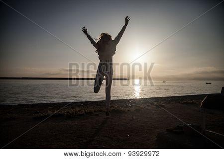 Girl Jumping Over Sunrise.
