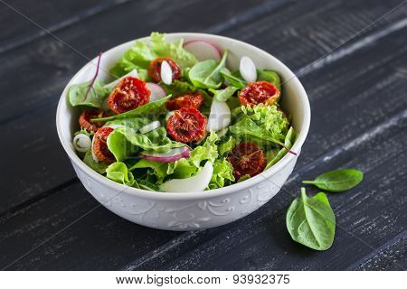 Salad With Fresh Vegetables, Garden Herbs And Sun-dried Tomatoes In A White Bowl On A Dark Wooden Ba