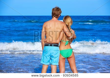 Blond young couple standing looking at the beach rear back view