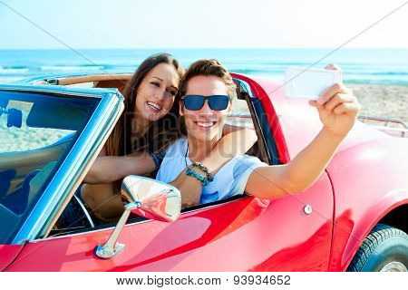 young couple selfie happy in a red convertible car at the beach