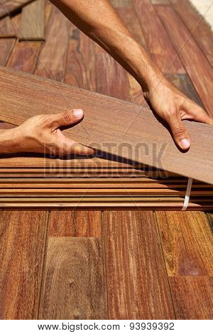 Ipe decking installation with carpenter hands holding tropical wood slats