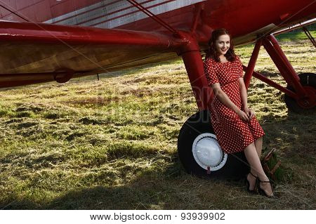 pin-up female sitting on wheel in red dress