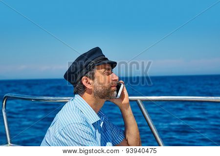 Captain cap sailor man talking mobile phone in boat sailing in the ocean sea