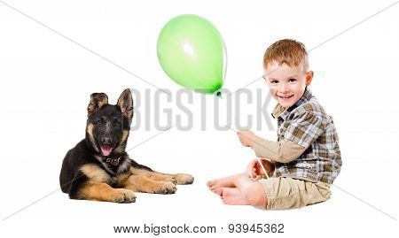 Happy boy and puppy German Shepherd playing with a balloon