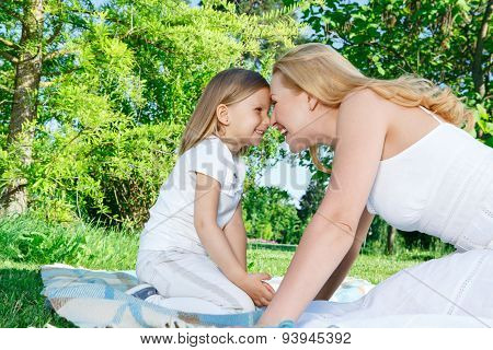 Mother and daughter sitting closely during picnic