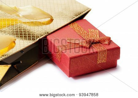 Gold Gift Bag And Red Gift Box Isolated On White. Selective Focus