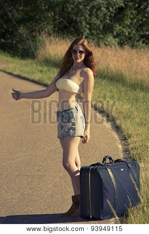 Beautiful young redhead woman waiting for a ride