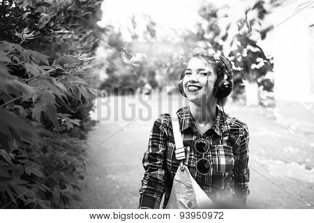 Hipster Girl Enjoying Music On Headphones And Smiling.