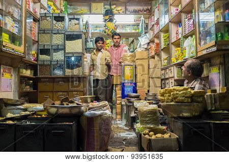JODHPUR, INDIA - 10 FEBRUARY 2015: Three men in various merchandise store talk business.