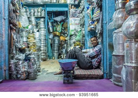 JODHPUR, INDIA - 10 FEBRUARY 2015: Worker sits and rests before closing time. Stores with kitchen pottery and other products made from metal are common on Asian markets.