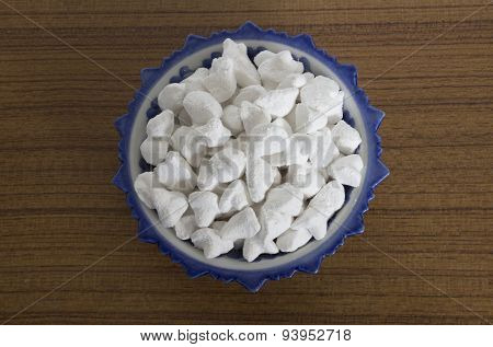 white clay filler or soft-prepared chalk or clay rich in porcelain cup on on wood board